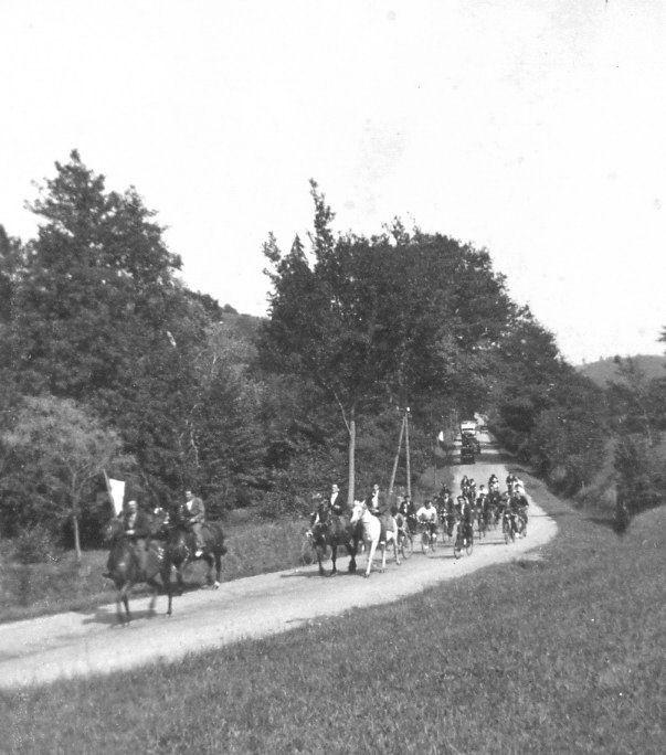 Accueil de l'abbé Monbeig : Cavaliers et cars précédant le cortège